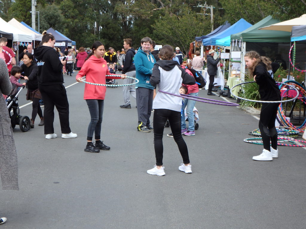 Festival patrons whirling Hula-hoops in the street
