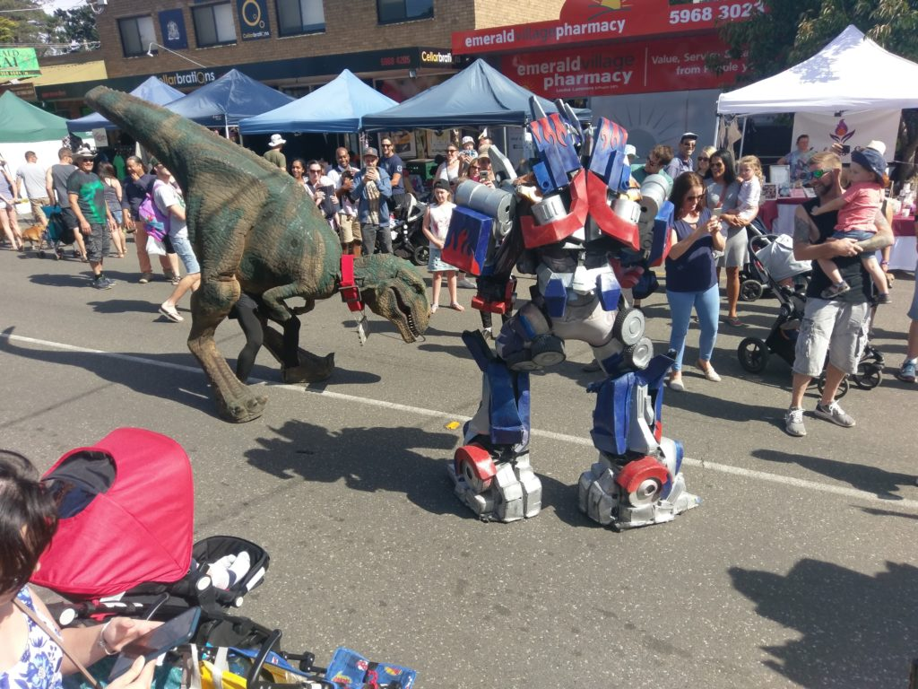 Transformers and Toby the T-Rex facing off in the main street